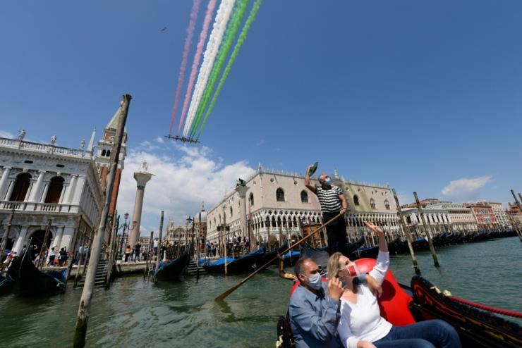 People taking a gondola ride and a gondolier wave as the Italian Air Force acrobatic unit perform over Venice