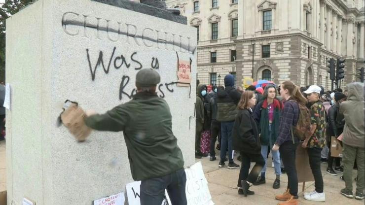 A man kicks away and rips down protest signs placed on a statue of Winston Churchill by anti-racism demonstrators