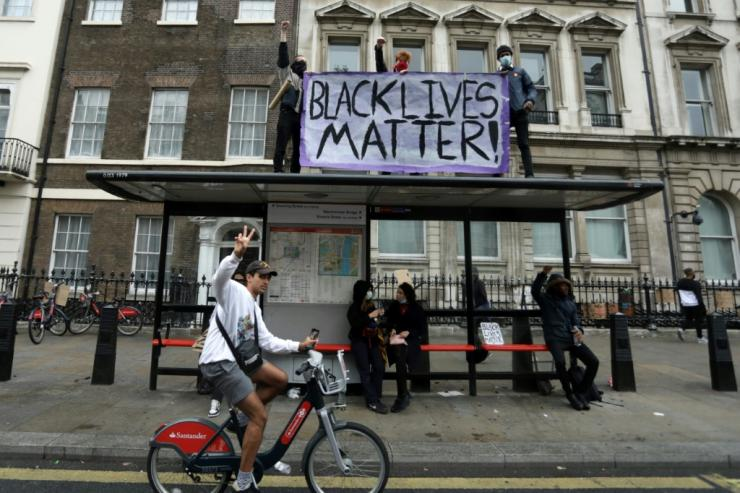 Protesters display a banner atop a bus stop after attending a demonstration outside the US Embassy