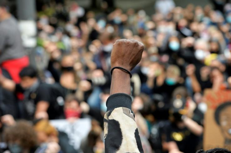 Protesters take a knee and raise their fists in a moment of silence for George Floyd and other victims of police brutality in Boston, Massachusetts