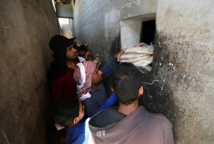 Syrians buy bread at a shop in the town of Binnish in the country's northwestern Idlib province