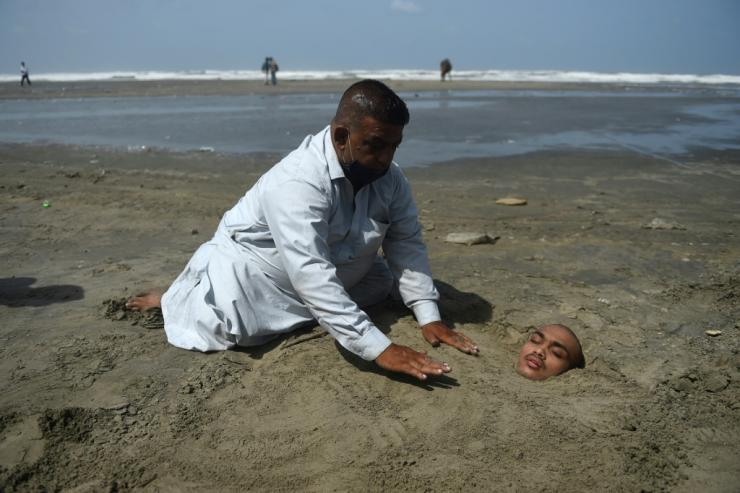 A man buries his paralysed son in sand on a beach in Karachi during the eclipse. Folklore has it if the eclipse passes over them they will be cured