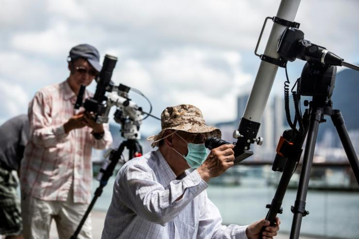 Skywatchers gathered on a Hong Kong waterfront to observe the spectacle