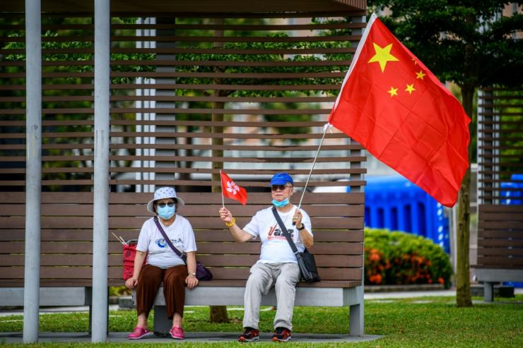 Pro-China supporters display Chinese and Hong Kong flags on the sidelines of a rally near the government headquarters in Hong Kong