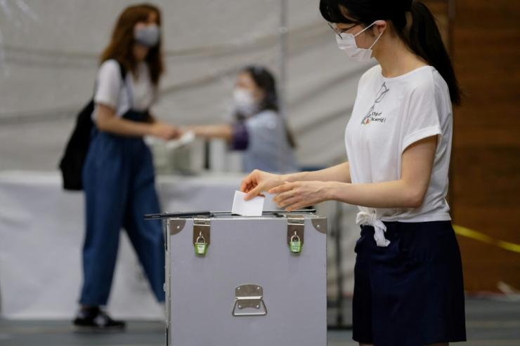 Voters in Tokyo are urged to use hand sanitiser after casting their ballot