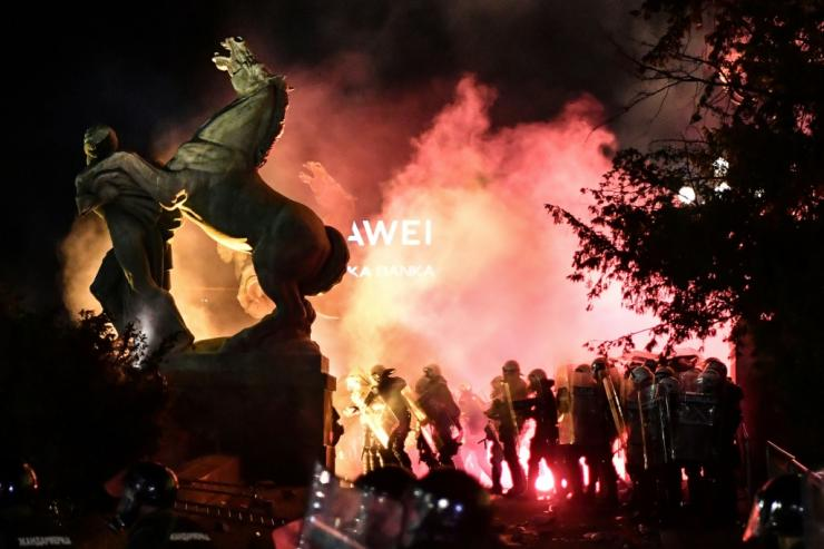 Police stand in tear gas smoke outside the National Assembly building in Belgrade, on July 10, 2020, during clashes with protesters at a  demonstration against a weekend curfew announced to combat a resurgence of COVID-19 infections