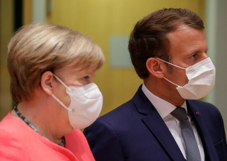 Germany's Chancellor Angela Merkel (L) and France's President Emmanuel Macron were described as looking annoyed after they left a late night meeting with the Netherlands' Prime Minister Charles Rutte