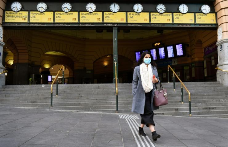 A commuter walks out of Melbourne's Flinders Street Station, wearing a mask