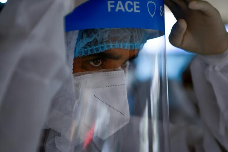 A health worker collects swab samples in the Mahaboudha area in Kathmandu