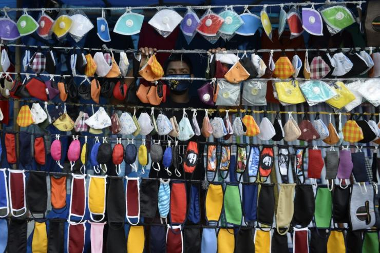A vendor arranges facemasks to sell on a roadside in Hyderabad, India