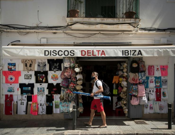 A man wearing a face mask walks in front of a store in Ibiza on July 31, 2020