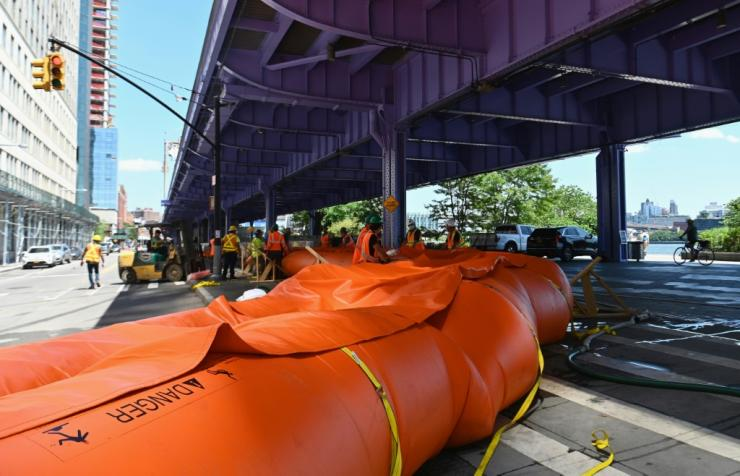 Workers set up temporary plastic flood barriers and sandbags known as 'Tiger Dams' in lower Manhattan to protect the area from flooding as tropical storm Isaias approaches New York City on August 3, 2020