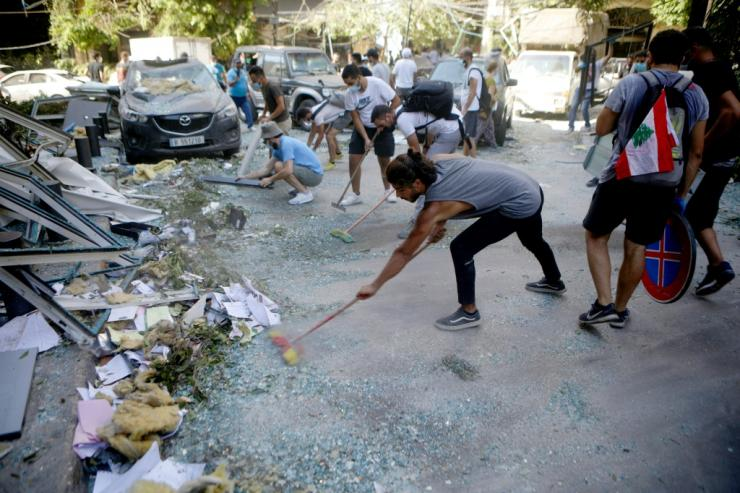 Despairing of receiving any help from the government, volunteers set about clearing the mangled metal and broken glass from their streets