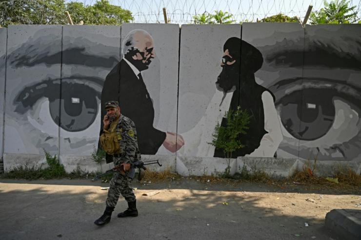 A soldier walks past a mural with images of US Special Representative for Afghanistan Reconciliation Zalmay Khalilzad (left) and Taliban co-founder Mullah Abdul Ghani Baradar