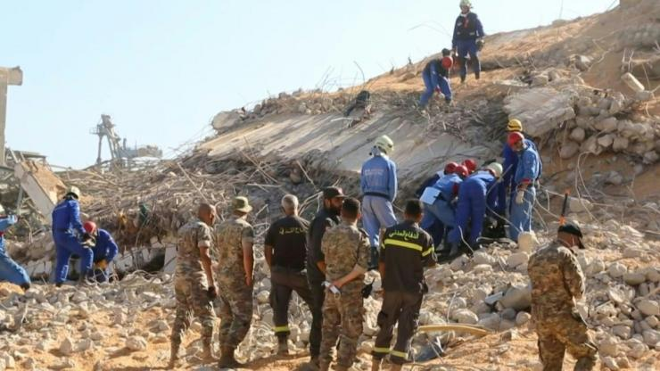 Ankle-deep in corn spilling out of a huge gutted silo, rescuers guide an excavator to clear access to a room where they believe Beirut port employees could still be alive. Three days after the monster explosion that disfigured the city in a few seconds, t