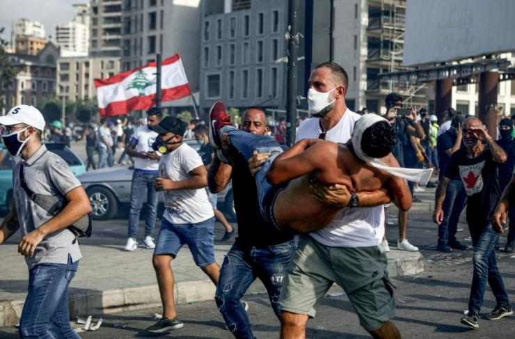 Lebanese basketball star Fadi al-Khatib carries a wounded demonstrator away from clashes in Beirut on Saturday, following a demonstration against a political leadership they blame for the monster explosion that killed more than 150 people