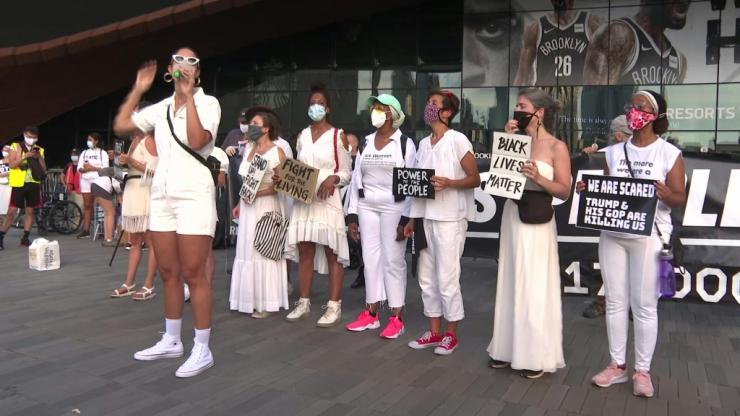"About a hundred protesters dressed in white gather in front of the Barclays Center in Brooklyn, New York, to denounce Donald Trump's response to the COVID-19 pandemic. The outbreak has left 175,000 people dead in the United States. ""It's a tragedy, I th"