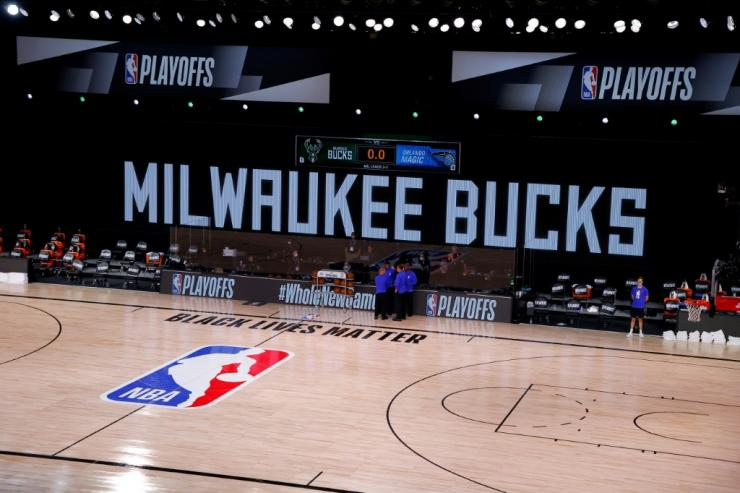 Referees huddled at the edge of an empty court as the Milwaukee Bucks and Orlando Magic did not arrive for the scheduled start of their NBA playoff contest