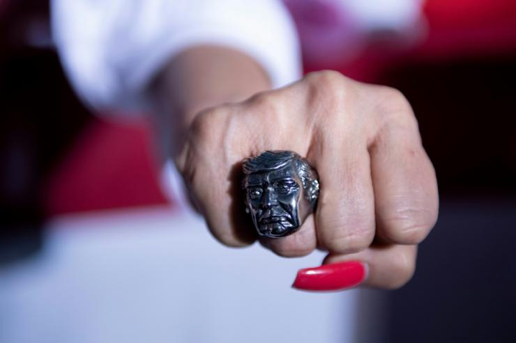 A supporter shows a ring featuring the face of US President Donald Trump during a campaign rally at the Minden-Tahoe airport in Minden, Nevada on September 12, 2020