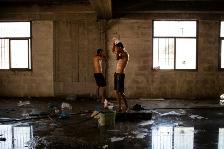 Migrants clean themselves inside an abandoned building