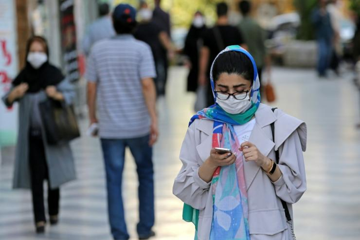 Shoppers, wearing protective masks due to the Covid-19 pandemic, walk past shops in Vali-asr Square in the Iranian capital Tehran on September 20, 2020
