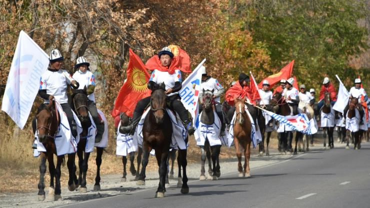 Supporters of the Birimdik (Unity) pro-government party wearing national 'Ak-kalpak' hats with flags ride horses on a road during a campaign event in the village of Koy-Tash, some 20 kms from the capital Bishkek