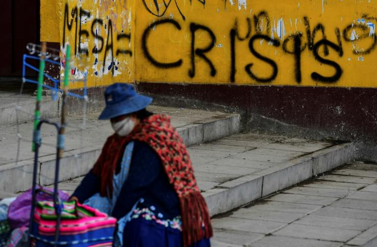 A woman is seen near a wall with graffiti against presidential candidate Carlos Mesa, in El Alto