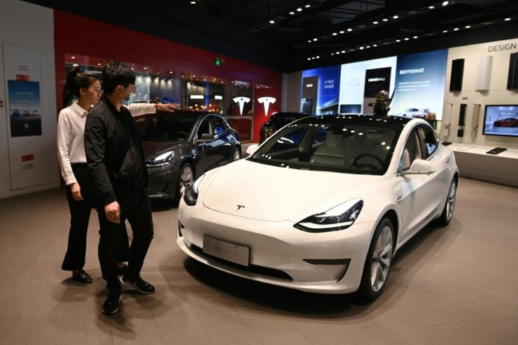 A man looks at a Tesla Model 3 in a Tesla showroom in Beijing on October 21; the electric car giant reported a doubling of profits on robust sales growth