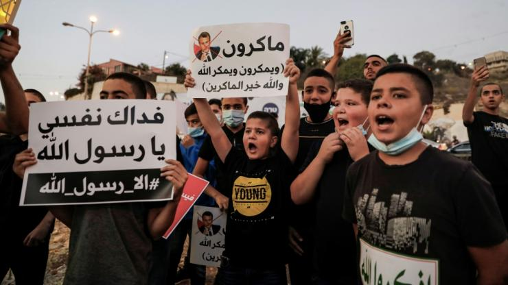 Arab Israeli Muslim demonstrators, clad in masks due to the COVID-19 coronavirus pandemic, protest against the comments by French President Emmanuel Macron, in the Arab town of Umm-Al Fahem in Northen Israel on Sunday