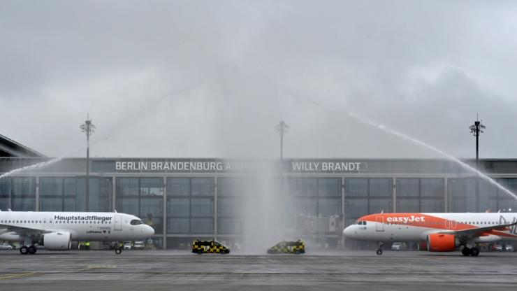 Fire engines sprayed water to greet the Lufthansa and Easyjet planes, the first flights to arrive at the new facility, opened nine years behind schedule