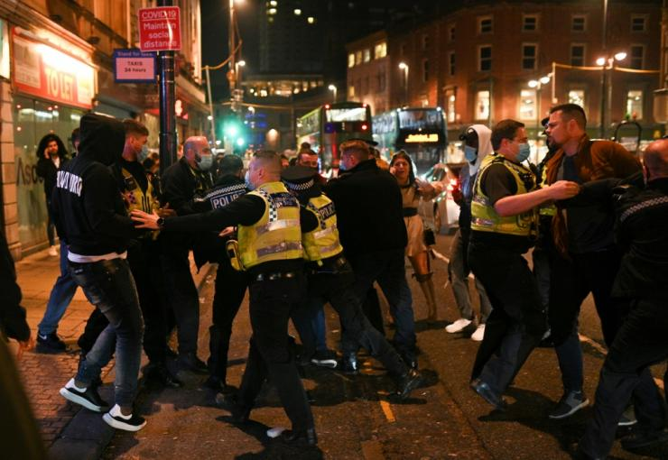 Police officers scuffle with revellers in the street after pub closing time in Leeds, northern England