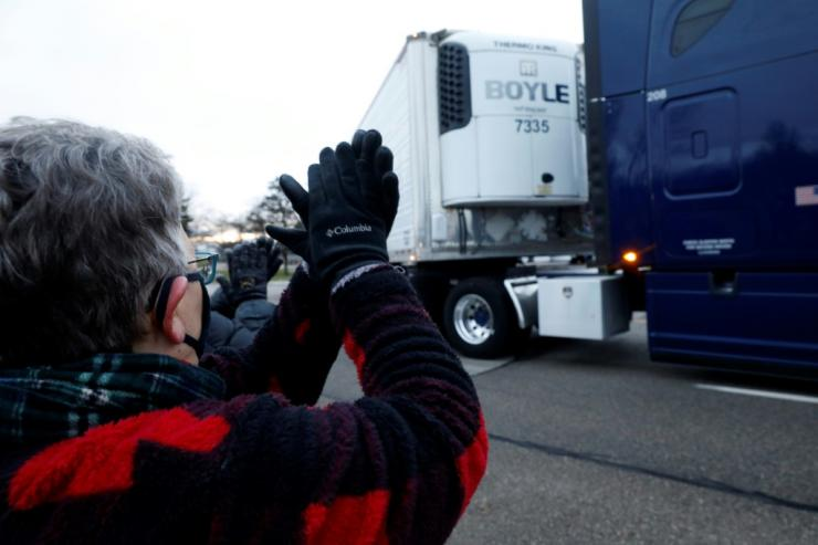 A bystander cheers as trucks carrying the first shipment of Covid-19 vaccine leave Pfizer's global supply facility in Kalamazoo, Michigan