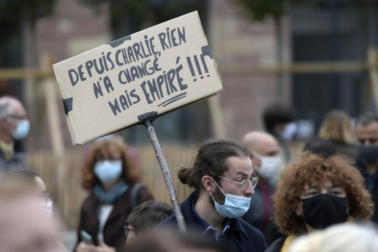 """A man holds a placard reading """"Nothing changed since Charlie"""" at a demonstration for schoolteacher Samuel Paty two days after he was beheaded by an attacker"""