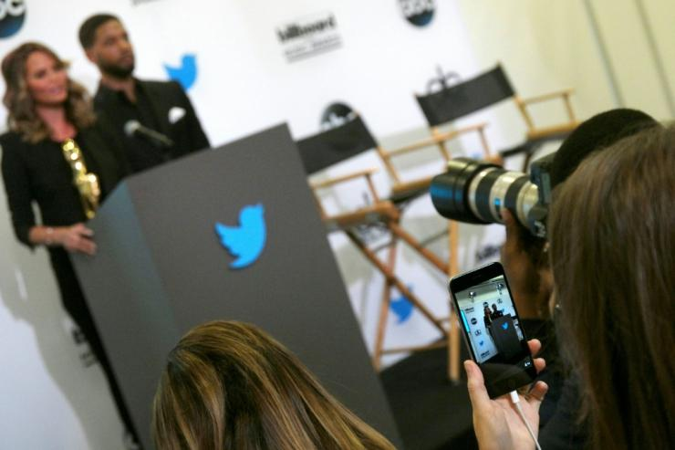 A woman uses the Twitter Periscope app on her mobile phone to live broadcast the announcement of the  Billboard Music Awards finalists in April 2015 in Santa Monica, California