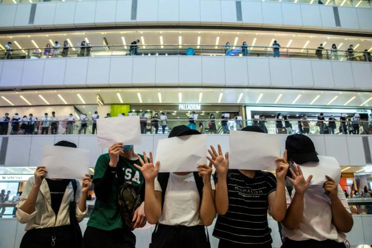 Hong Kong protesters hold up blank papers during a demonstration in response to the sweeping new national security law which outlaws a host of political views