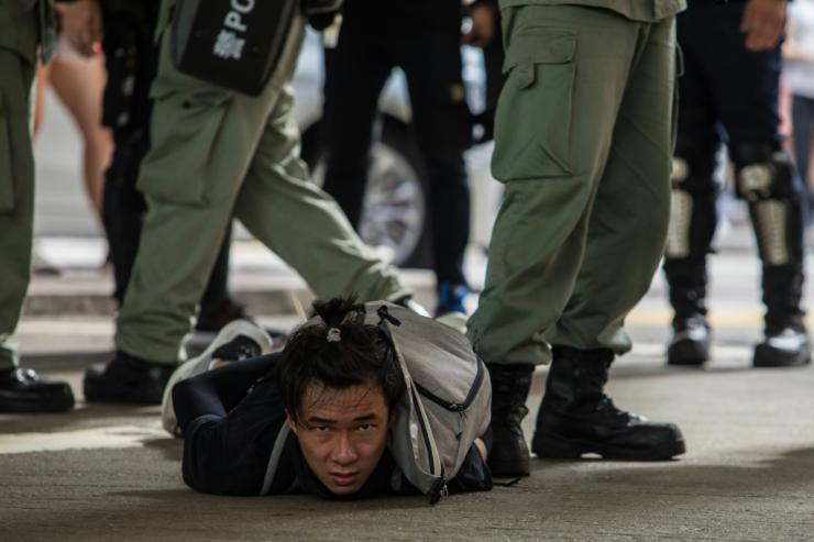 Hong Kong riot police detain a man as they clear protesters taking part in a July 1, 2020 rally against the new national security law imposed by Beijing