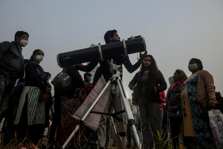"People stand in a queue to see a ""great conjunction"" of Jupiter and Saturn, in Kolkata, India on December 21, 2020"