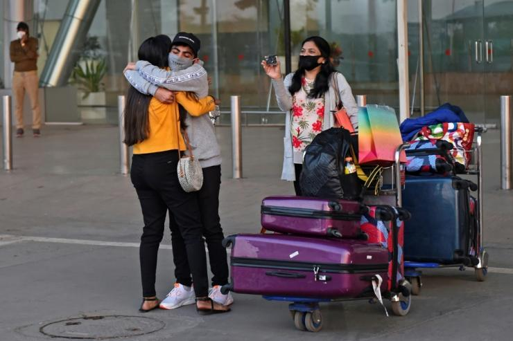 A passenger arriving from Britain is hugged by a relative at Sardar Vallabhbhai Patel International Airport in Ahmedabad before the ban on UK arrivals was imposed