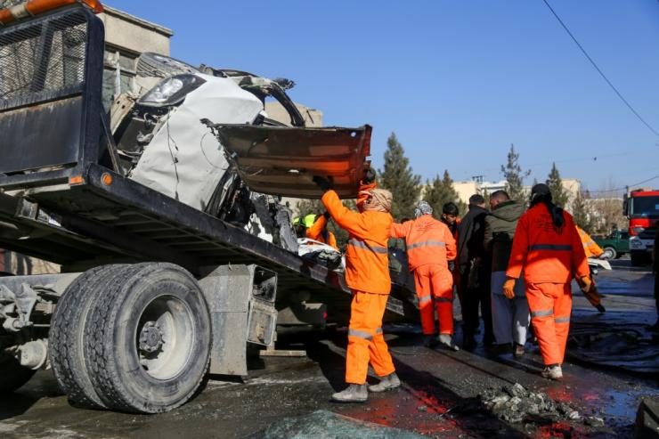 Municipal workers clean up debris from the site of a bomb attack in Kabul that killed five people, including two women prison doctors