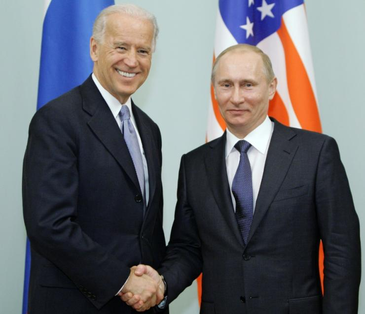 Biden (l) shakes hands with Putin in 2011 while serving as Vice-President to Barack Obama