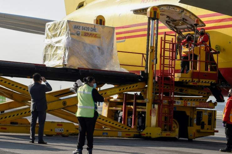 Workers unload Mexico's first batch of Pfizer-BioNTech vaccines from a plane at the capital's international airport