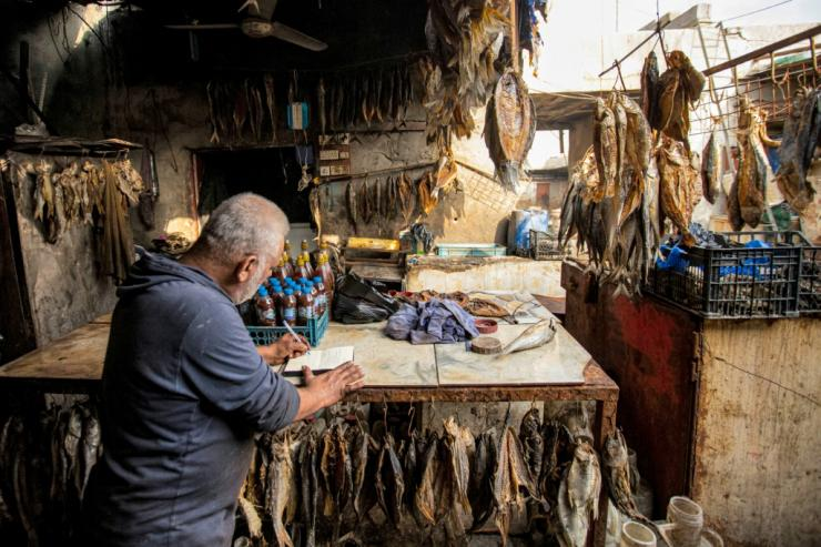A fishmonger writes his Christmas message at his stall in Basra port