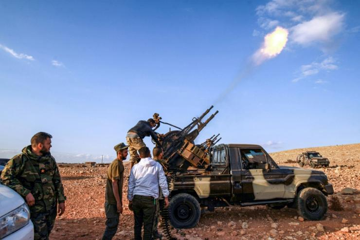 Libyan fighters loyal to eastern strongman Khalifa Haftar fire guns during a funeral of a comrade in November 1, 2020; Haftar has urged his troops 'drive out' Turkish forces