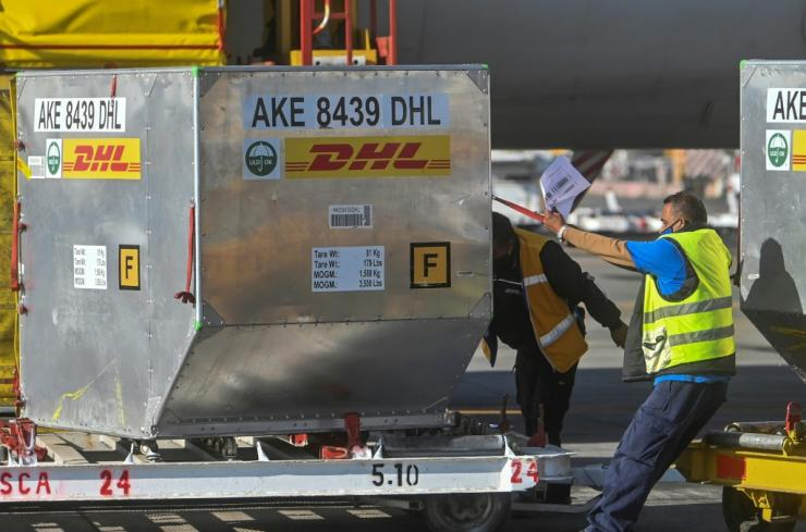 Workers at the Mexico City airport unload containers from an airplane carrying the second shipment of the Pfizer/BioNTech COVID-19 vaccine for the country