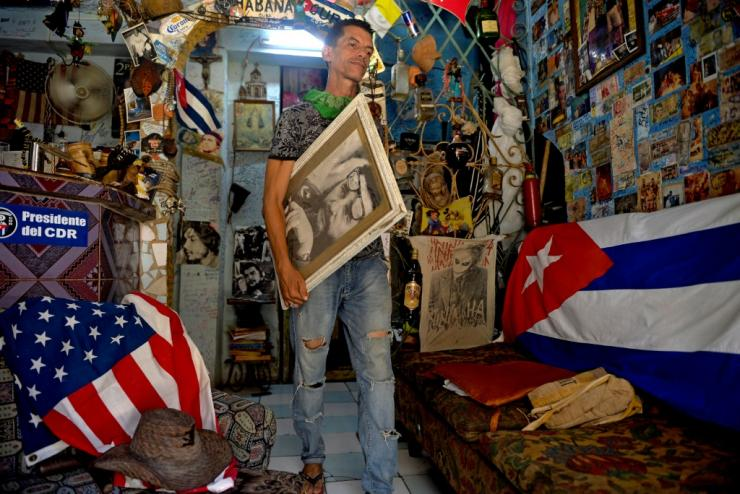 A man carries a portrait of late Cuban  leader Fidel Castro next to Cuban and US flags at his house in Havana in July 2020
