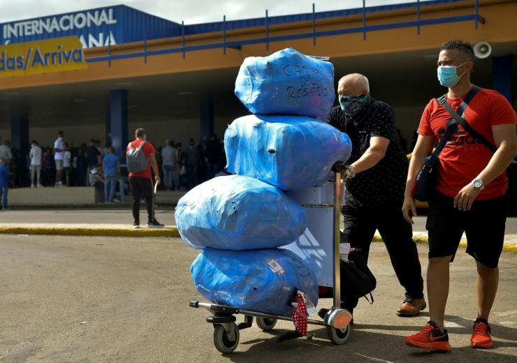 Cuban-Americans carry luggage as they leave Havana's Jose Marti International Airport in November 2020 amid growing limitations on travel