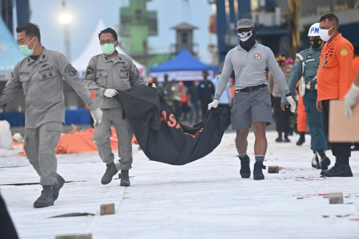 Forensic policemen carry a bag containing debris from the crashed plane