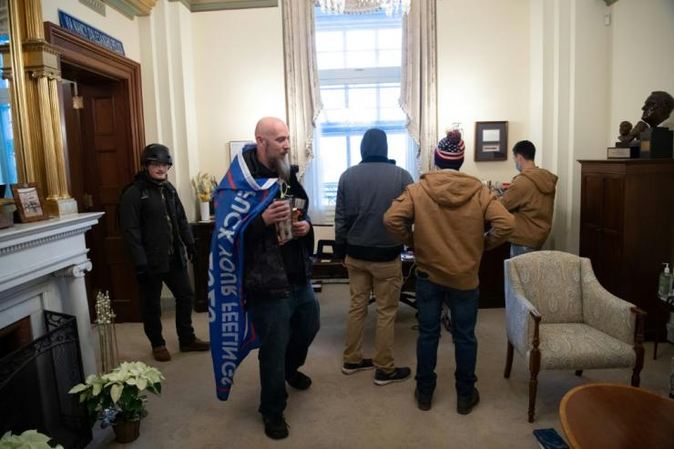 Supporters of US President Donald Trump walk through the office suite of Speaker of the House Nancy Pelosi after breaking through police lines and entering the US Capitol