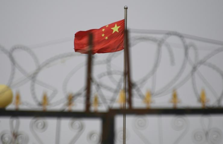 The Chinese flag behind razor wire at a housing compound in Yangisar in China's western Xinjiang region in June 2019
