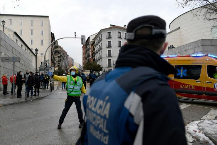 Emergency personnel secure the area surrounding a building damaged in an explosion in Madrid